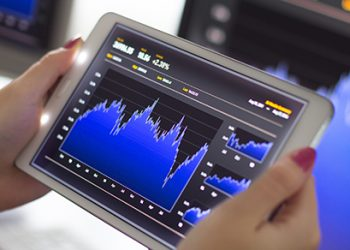 Business woman holding a digital tablet pc analyzing stock market graph. Selective focus.